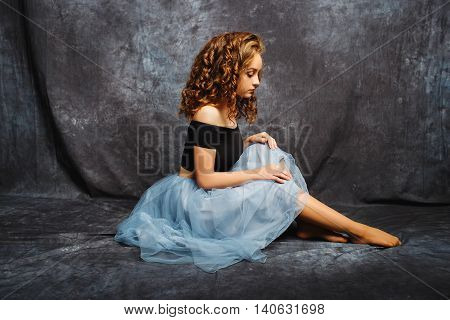 Ballerina Tying Ballet Shoes.Ballet dancer in blue skirt