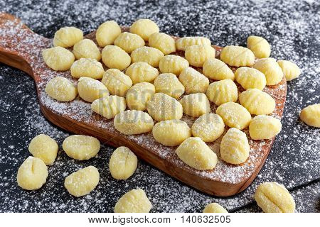 Uncooked homemade gnocchi on wooden cutting floured board.
