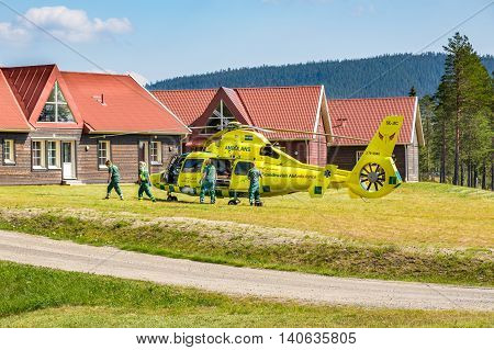 Klövsjö, Jämtland, Sweden - July 25, 2016: Ambulance helicopter and paramedics rescue. Emergency response team with ambulance helicopter lands beside buildings.
