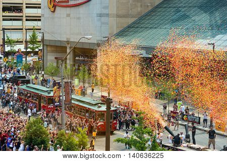 CLEVELAND OH - JUNE 22 2016: Confetti cannons signal the start of the Cavaliers NBA championship parade next to the Q with eager crowds thronging the route.