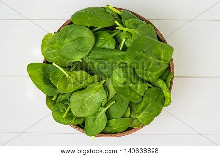 Spring spinach leaves in the bowl. White wooden background. Top view