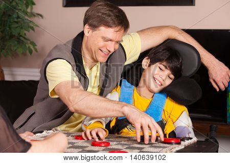 Young biracial disabled boy in wheelchair playing checkers with father at home