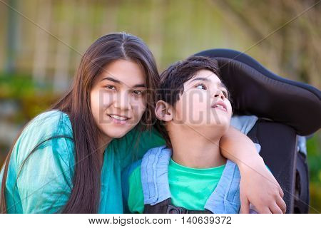 Smiling teenage girl hugging disabled nine year old brother in wheelchair outdoors