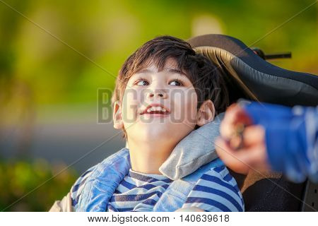 Handsome disabled nine year old boy sitting in wheelchair outdoors looking up into sky