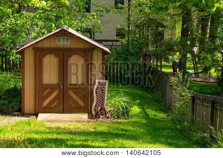 A small storage barn stands in a shady backyard