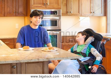 Disabled boy in wheelchair in kitchen with older brother ready to have lunch of hamburger and french fries