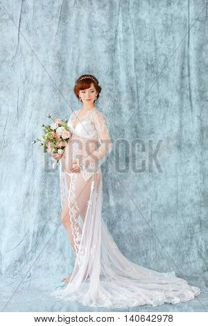 Pregnant Woman Holding Flowers, Standing In The Boudoir Dress On A Blue Background.
