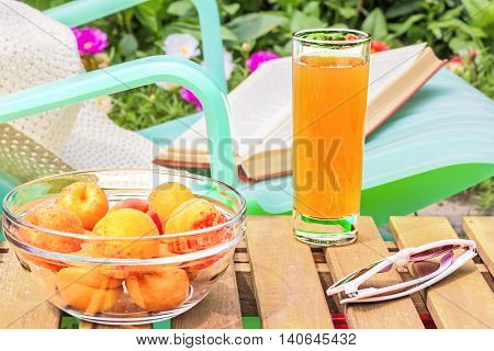 Relax in the flowering garden on a sunny summer day. Glass of juice a bowl of yellow ripe apricots and sun glasses on a wooden table in the foreground. In the background is green chaise longue a book and a white hat near blooming flower bed