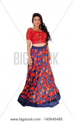 A beautiful East Indian woman in a long blue and red skirt and red top standing isolated for white background.