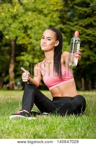 Beautiful slim healthy young brunette woman working out in the park.