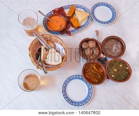 Four bowls filled with Spanish appetizers known as tapas