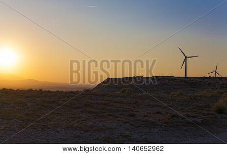 Electric wind turbines farm with sunset light on arid landscape Spain