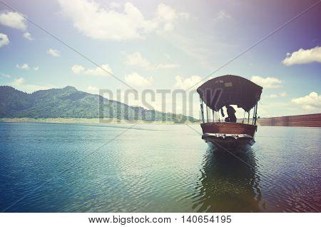 A fishing boat approaches shore area at Khun Dan dam Nakohn Nayok Thailand with light effect