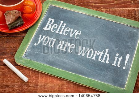 Believe you are worth it - Motivational advice on a slate blackboard with chalk and cup of tea