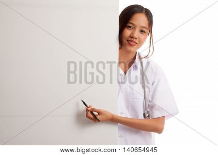 Young Asian Female Doctor Peeking From Behind Blank Sign Point With A Pen