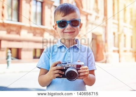 Small boy in sunglasses is posing with a photo camera in his hands on the background of old buildings during walk on a summer sunny day