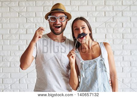 Close-up of merry couple holding paper moustache and glasses against a white concrete background