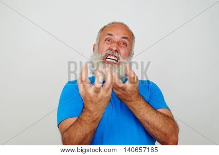 Aged bearded man is grimacing at the camera expressing extreme nervousness isolated on white background
