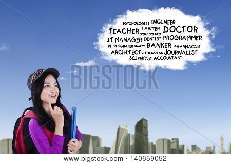 Beautiful Asian high school student thinking the dream jobs on the speech bubble