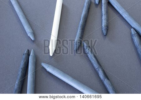 This is a photograph of black,Grey and White crayons placed on colorful craft paper