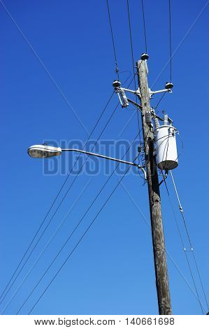 power pole with street lamp under blue sky