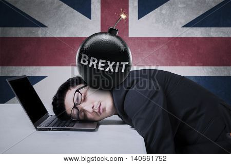 Frustrated businessman sleeping on laptop with text of Brexit on the bomb at his head shot with UK flag background