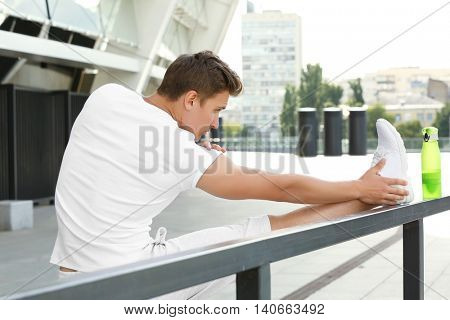 Young man doing exercises near handrail