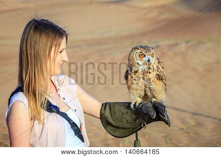Desert Eagle Owl sits on a young woman's hand at Dubai Desert Conservation Reserve, UAE