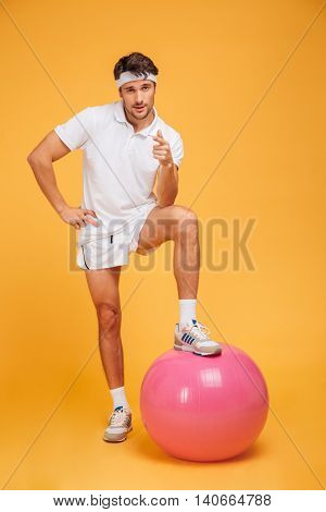 Young handsome sportsman with one foot on fitness ball and pointing at camera isolated on the orange background