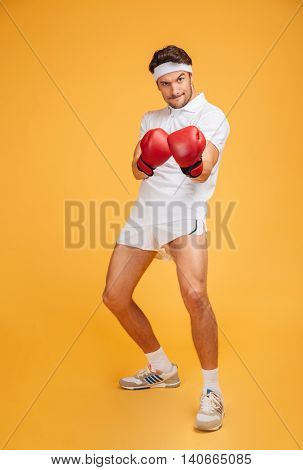Full length of serious young man boxer standing in red gloves over yellow background