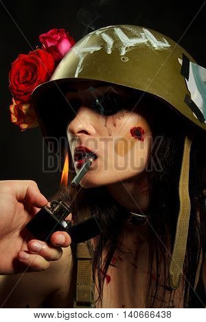 Glamour military girl smoking a cigar over black background
