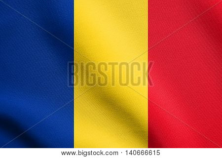 Flag of Romania waving in the wind with detailed fabric texture. Romanian national flag.