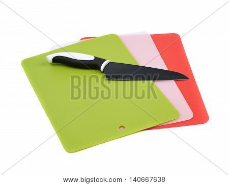 Pile of multiple plastic cutting boards with a knife lying over it, composition isolated over the white background