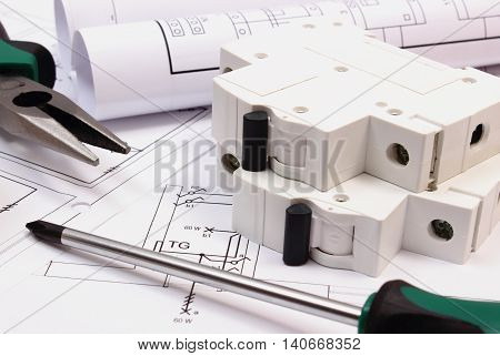 Metal pliers screwdriver electric fuse and rolls of diagrams on electrical construction drawing of house concept of building house