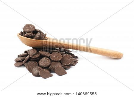 Pile of cooking chocolate teardrop shaped chips with a serving wooden spoon over it, composition isolated over the white background