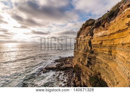 Cliffside erosion with ocean background at Sunset Cliffs in San Diego, California.