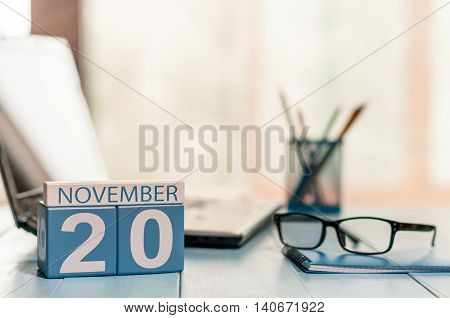 November 20th. Day 20 of month, calendar on freelancer workspace background. Autumn time. Empty space for text.