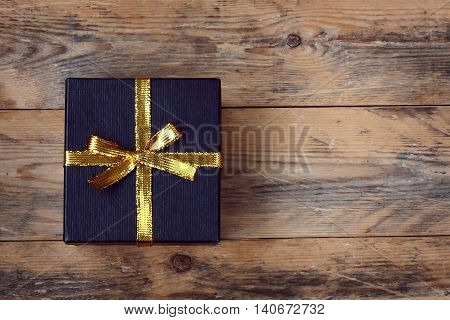black gift box with golden ribbon bow on wooden plank table