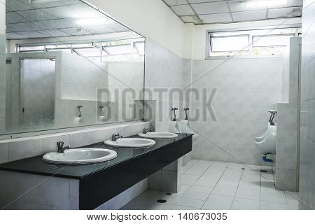 Old grungy dirty interior public gentlemen restroom