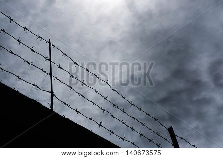 Silhouette barbed wire against dark gloomy overcast sky