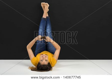 Beautiful woman lying in the floor and texting a sms