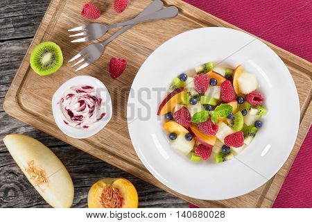 yummi fruit and berry summer dessert salad decorated with mint leaves in white wide rim dish on wooden cutting boards and cream sauce bilberry dip view from above close-up
