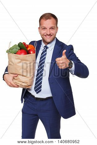 Smiling young businessman hold shopping bag full of groceries isolated at white background. Healthy food shopping. Paper package with vegetables and fruits, happy man buyer show thumb up