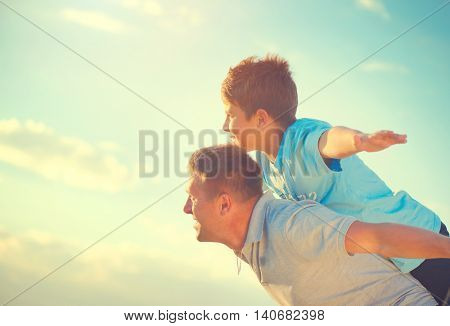 Happy Father and Son having fun over beautiful sky outdoors. Laughing Dad with Little Boy enjoying nature together. Joyful Family. Free, freedom concept. Summer Holidays, vacation