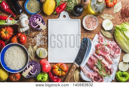 Ingredients for cooking healthy dinner. Raw lamb meat chops, rice, vegetables, oil, herbs and spices over rustic wooden background with white ceramic board in center. Top view, copy space