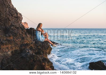 Young blond woman tourist in blue dress sittig on rocks by the sea at sunset. Kleopatra beach, Alanya, Mediterranean region, Turkey.