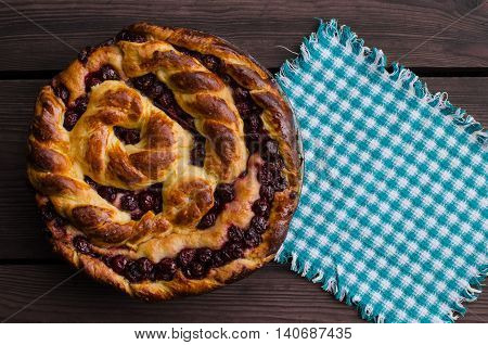 Homemade pie with cherries on wooden table in rustic style. Organic food.