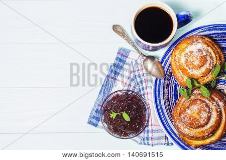 Two spiral tasty buns with coconut chips and mint and cup of black coffee. Delicious breakfast sweet rolls and coffee. Coffee in blue cup