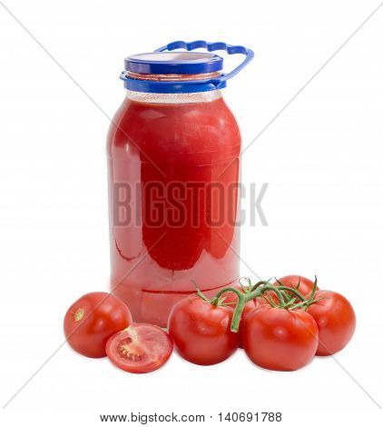 Tomato juice in glass jar with a blue plastic handle bunch of tomatoes whole and half a tomato on a light background