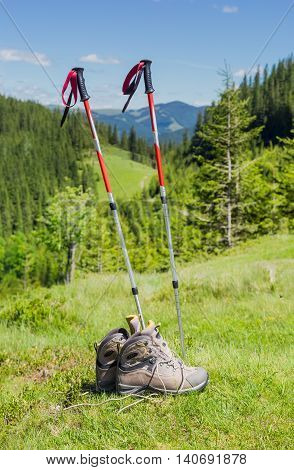 Pair of trekking poles made from three aluminum sections and pair of light brown leather trekking boots on a background of forested mountains
